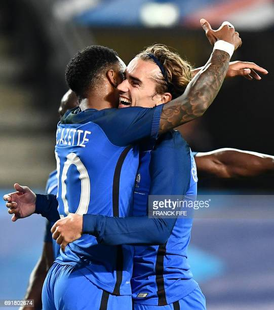 France's forward Antoine Griezmann celebrates with teammate France's forward Alexandre Lacazette after scoring a goal during the friendly football...