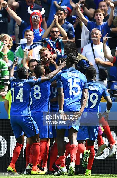 France's forward Antoine Griezmann celebrates with teammates after he scored during the Euro 2016 round of 16 football match between France and...