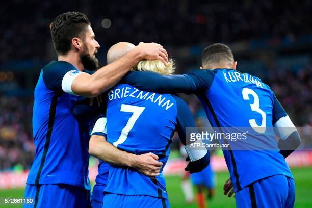 France's forward Antoine Griezmann celebrates with teammates France's forward Olivier Giroud and France's defender Layvin Kurzawa after scoring a...