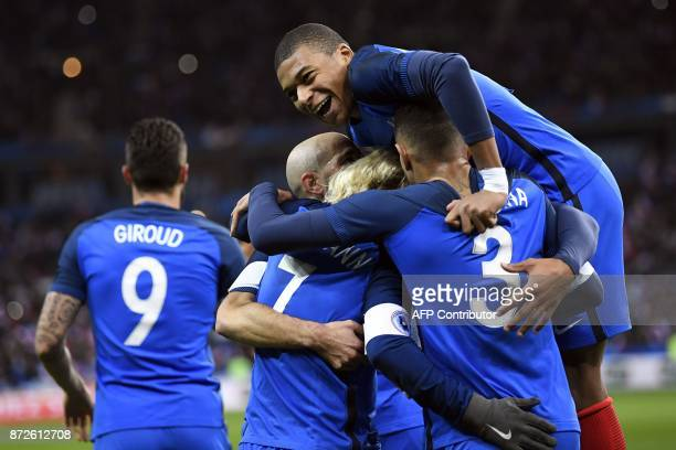 France's forward Antoine Griezmann celebrates with teammates including France's forward Kylian Mbappe after scoring a goal during the friendly...