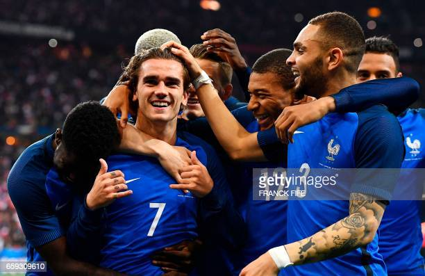 TOPSHOT France's forward Antoine Griezmann is congratuled by teammates after a goal that was finally disallowed for offside during the friendly...