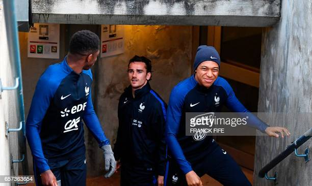 France's forward Antoine Griezmann jokes with France's forward Kylian Mbappe and France's forward Ousmane Dembele during a training session at the...