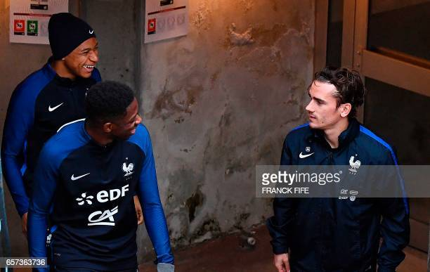 France's forward Antoine Griezmann jokes with France's forward Kylian Mbappe and France's forward Ousmane Dembele before a training session at the...
