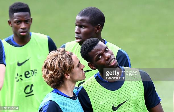 France's forward Antoine Griezmann jokes with France's midfielder Paul Pogba during a training session at the Roazhon Park stadium in Rennes on June...