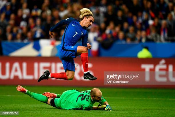 France's forward Antoine Griezmann jumps over Belarus' goalkeeper Sergei Chernik as he scores a goal during the FIFA World Cup 2018 qualification...