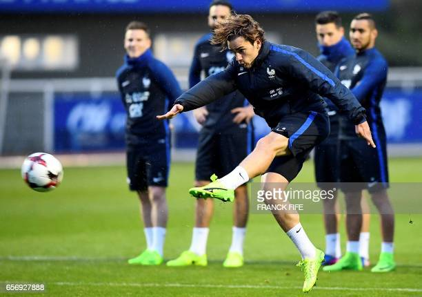 TOPSHOT France's forward Antoine Griezmann kicks the ball during a training session in Clairefontaine on March 23 near Paris as part of the team's...