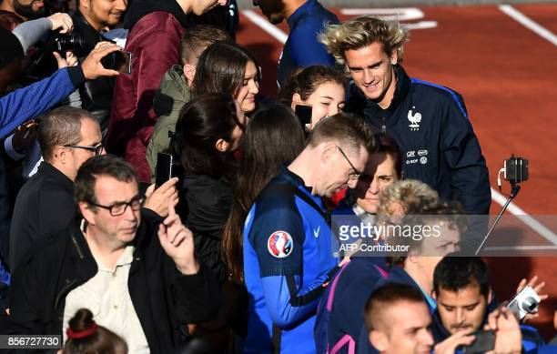 France's forward Antoine Griezmann poses for photographs with with fans before a training session in ClairefontaineenYvelines on October 2 2017 as...