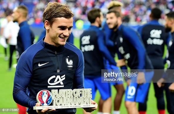France's forward Antoine Griezmann receives the trophy for best player of Euro 2016 before the FIFA World Cup 2018 qualifying football match France...