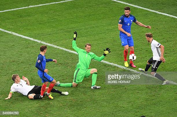 France's forward Antoine Griezmann scores a goal past Germany's goalkeeper Manuel Neuer during the Euro 2016 semifinal football match between Germany...