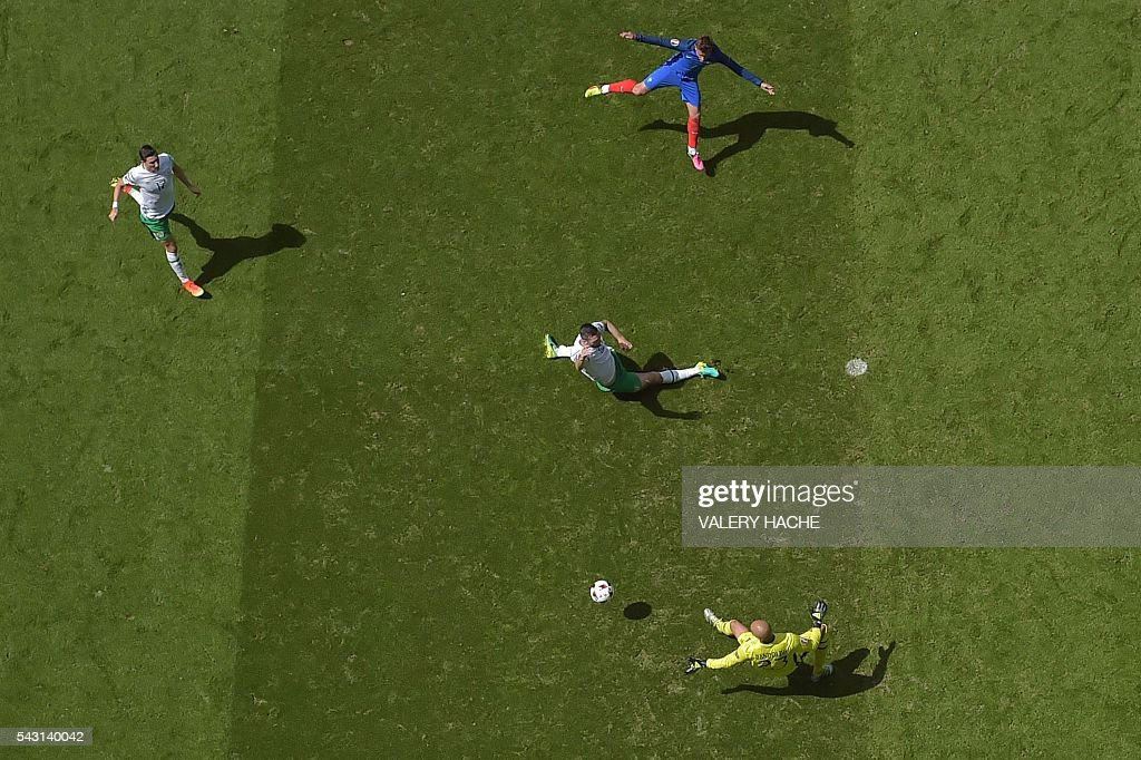 France's forward Antoine Griezmann (top) scores against Ireland's goalkeeper Darren Randolph (bottom) during the Euro 2016 round of 16 football match between France and Republic of Ireland at the Parc Olympique Lyonnais stadium in Décines-Charpieu, near Lyon, on June 26, 2016. / AFP / Valery HACHE