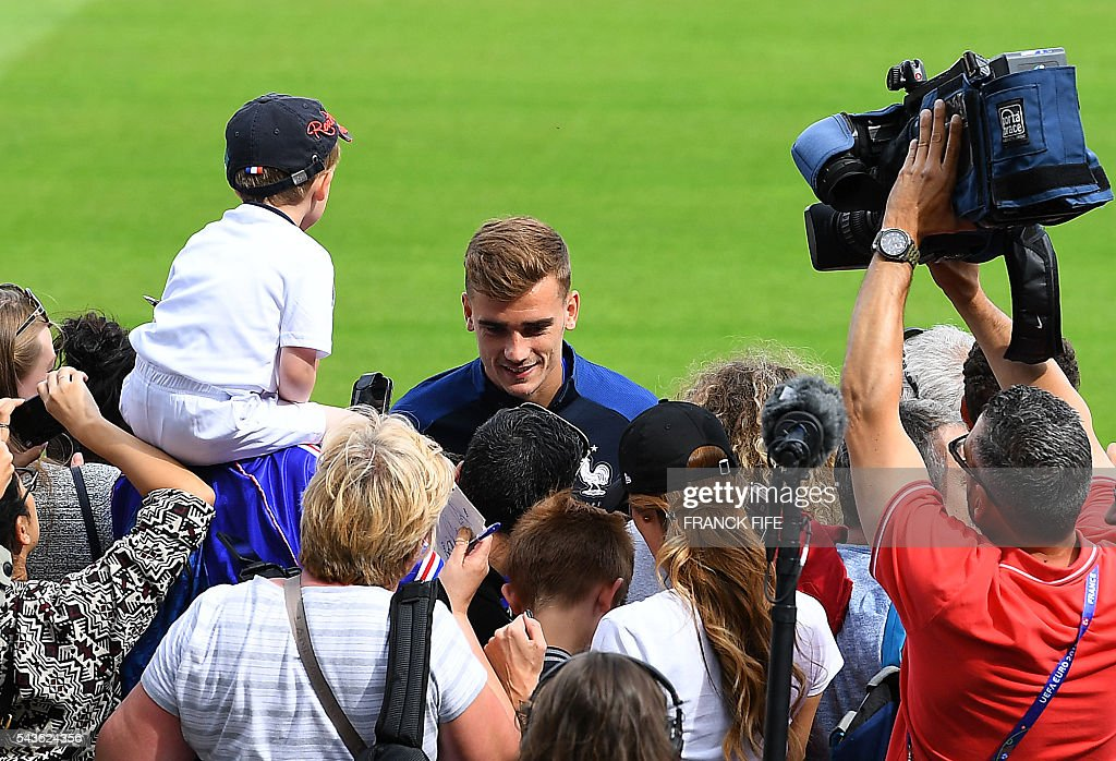 France's forward Antoine Griezmann (C) signs autographs before a training session in Clairefontaine-en-Yvelines, southwest of Paris, on June 29, 2016, during the Euro 2016 football tournament. / AFP / FRANCK