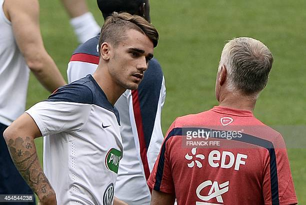 France's forward Antoine Griezmann speaks with France's coach Didier Deschamps during a training session of France's football team on September 3 on...