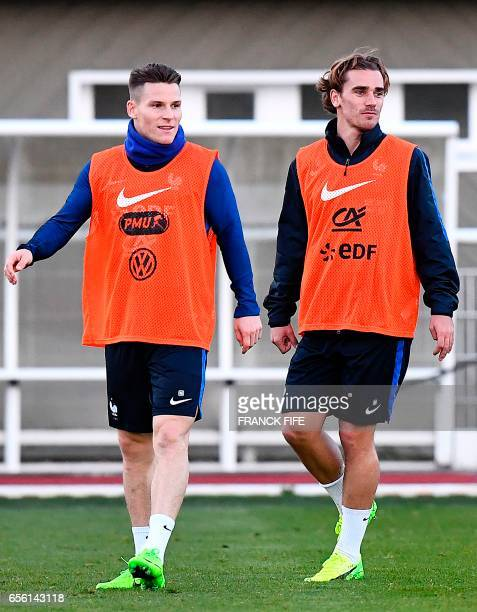 France's forward Antoine Griezmann speaks with France's forward Kevin Gameiro during a training session in Clairefontaine near Paris on March 21 as...
