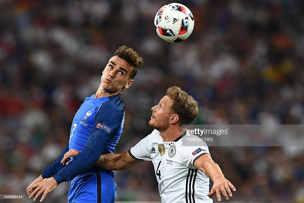 TOPSHOT France's forward Antoine Griezmann vies for the ball against Germany's defender Benedikt Hoewedes during the Euro 2016 semifinal football...