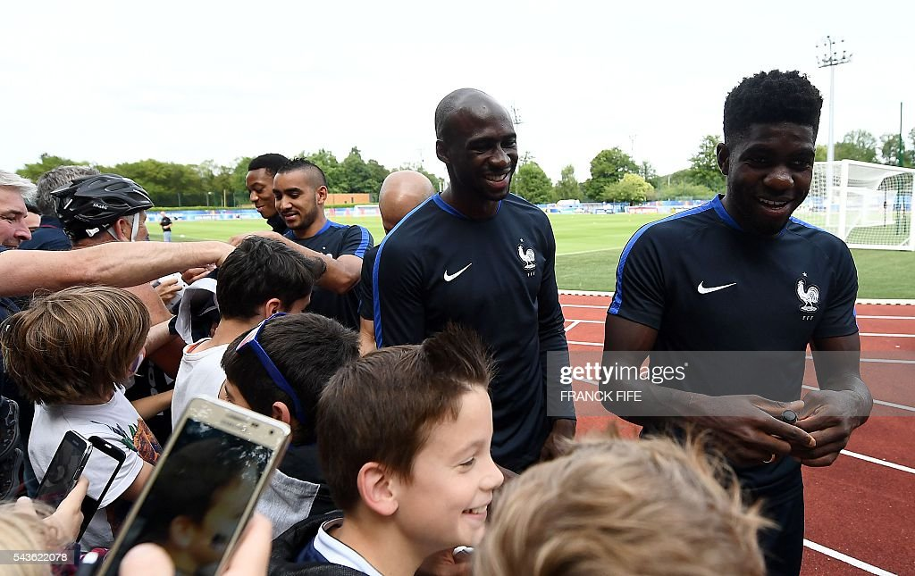 France's forward Dimitri Payet, France's defender Eliaquim Mangala and France's defender Samuel Umtiti sign autographs before a training session in Clairefontaine-en-Yvelines, southwest of Paris, on June 29, 2016, during the Euro 2016 football tournament. / AFP / FRANCK