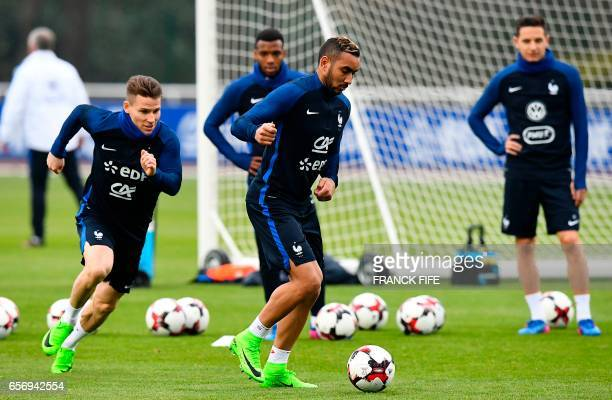 France's forward Dumitri Payet controls the ball next to France's forward Florian Thauvin and France's forward Kevin Gameiro during a training...