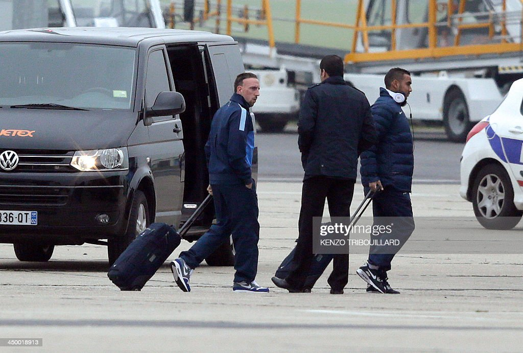 France's forward Franck Ribery (L) and midfielder Dimitri Payet (R) walk on the tarmac of Le Bourget airport, Paris suburb, on November 16, 2013 a day after the FIFA World Cup 2014 qualifying football match Ukraine vs France in Kiev. Ukraine won 2-0.