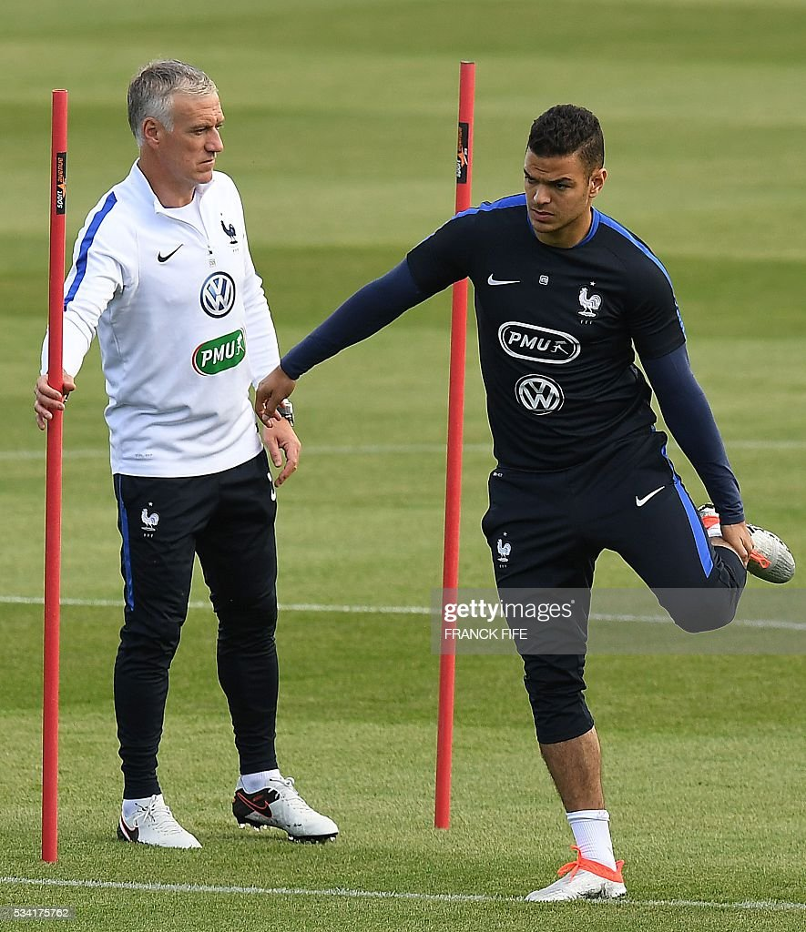 France's forward Hatem Ben Arfa (R) stretches next to France's head coach Didier Deschamps (L) during a training session in Clairefontaine as part of the team's preparation for the upcoming Euro 2016 European football championships, on May 25, 2016. / AFP / FRANCK
