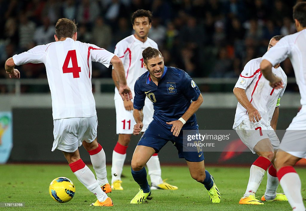 France's forward Karim Benzema (C) grimaces next to Georgia's defender Guram Kashia during the FIFA World Cup 2014 qualifying football match Georgia vs France on September 6 2013 at the Boris Paichadze stadium in Tbilisi.