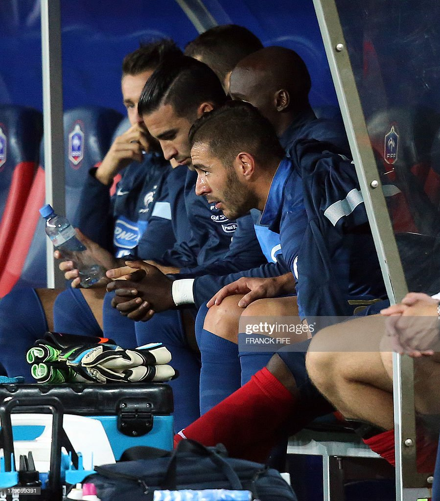 France's forward Karim Benzema (R) sits in the Bench after leaving a pitch during the FIFA World Cup 2014 qualifying football match Georgia vs France on September 6 2013 at the Boris Paichadze stadium in Tbilisi.