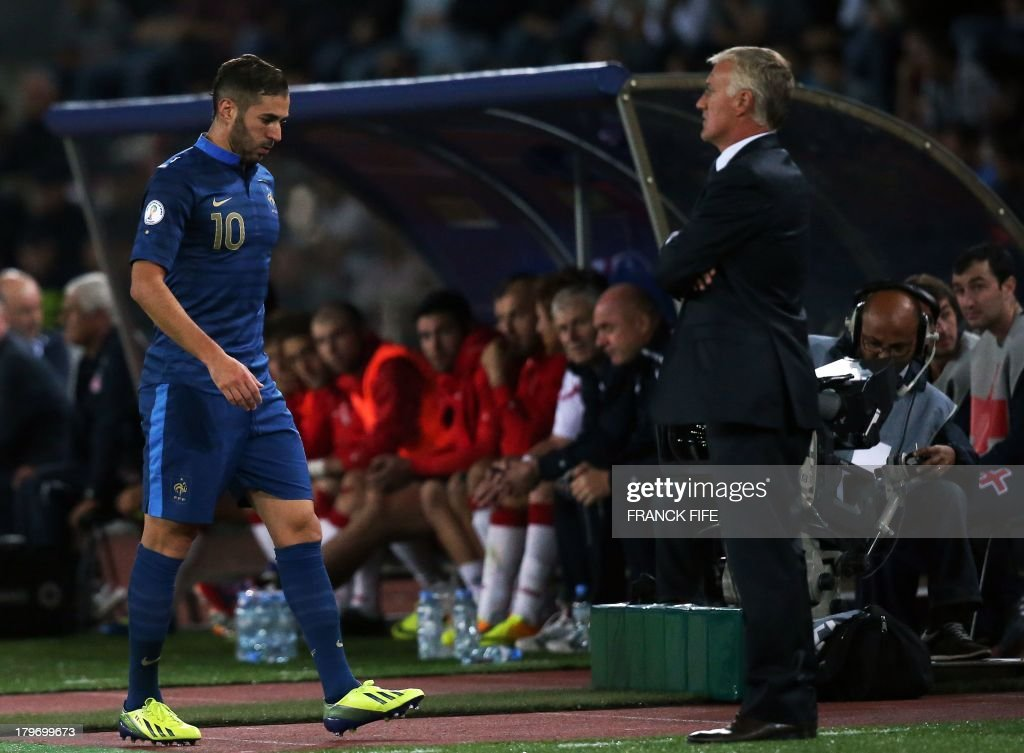 France's forward Karim Benzema (L) walks in front head coach Didier Deschamps during the FIFA World Cup 2014 qualifying football match Georgia vs France on September 6 2013 at the Boris Paichadze stadium in Tbilisi.