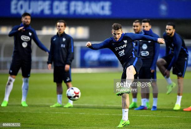 France's forward Kevin Gameiro kicks the ball during a training session in Clairefontaine on March 23 near Paris as part of the team's preparation...