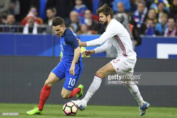 France's forward Kevin Gameiro vies with Spain's defender Gerard Pique during their friendly football match France vs Spain at the stade de France in...