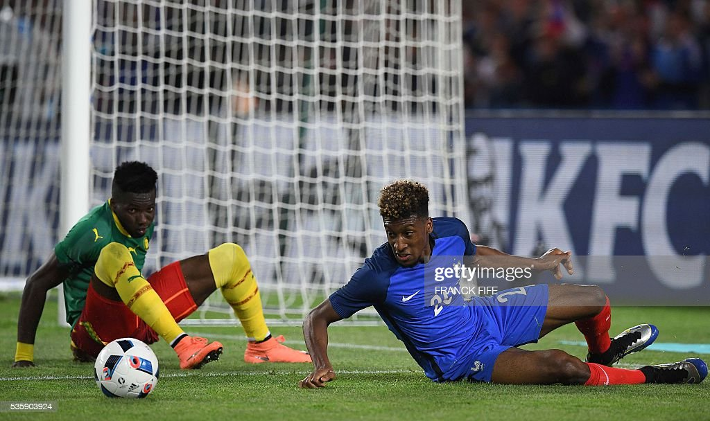 France's forward Kingsley Coman (R) fights for the ball with Cameroon's defender Adolphe Teikeu during the International friendly football match between France and Cameroon at the Beaujoire stadium, in Nantes, western France, on May 30, 2016 as part of the French team's preparation for the upcoming Euro 2016 European football championships. / AFP / FRANCK