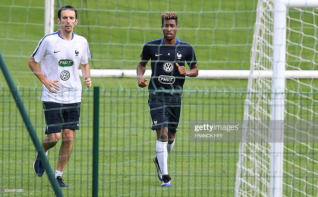 France's forward Kingsley Coman (R) runs with a staff member during a training session in Clairefontaine en Yvelines on May 26, 2016, as part of the team's preparation for the upcoming Euro 2016 European football championships. / AFP / FRANCK