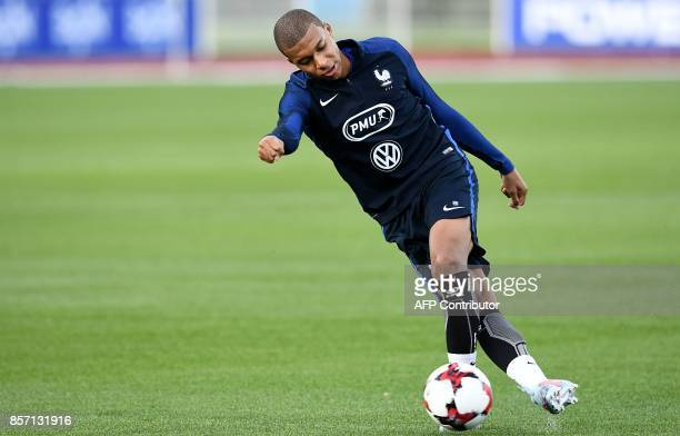 France's forward Kylian Mbappe controls the ball during a training session in ClairefontaineenYvelines on October 3 in preparation for the team's...