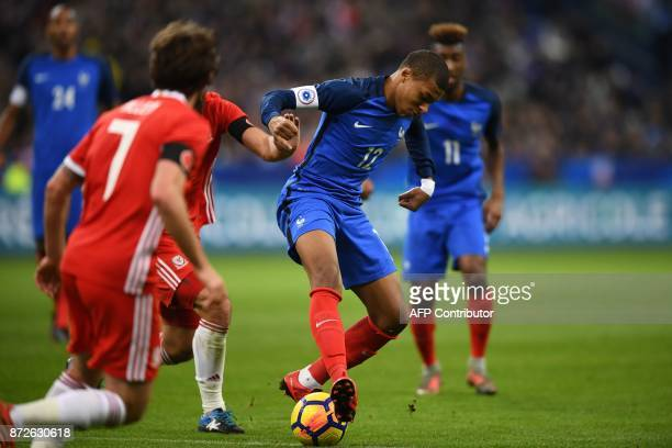 France's forward Kylian Mbappe controls the ball during the friendly football match between France and Wales at the Stade de France stadium in...