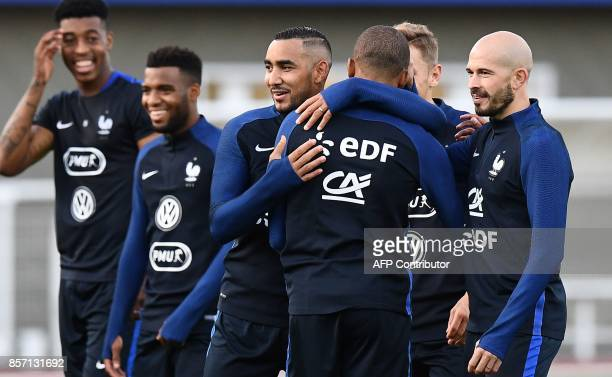 France's forward Kylian Mbappe hugs France's forward Dimitri Payet next to France's defender Christophe Jallet during a training session in...