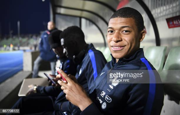 France's forward Kylian Mbappe poses on the bench next to France's forward Ousmane Dembele and France's defender Layvin Kurzawa before the FIFA World...