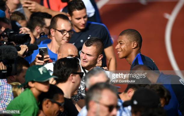 TOPSHOT France's forward Kylian Mbappe poses with fans during a training session in Clairefontaine en Yvelines on August 28 as part of the team's...