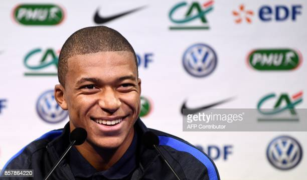 France's forward Kylian Mbappe reacts as he speaks during a press conference in ClairefontaineenYvelines on October 5 as part of the team's...