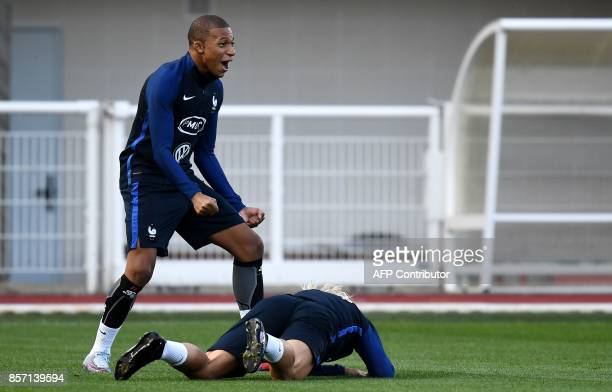 France's forward Kylian Mbappe reacts next to France's forward Antoine Griezmann during a training session in ClairefontaineenYvelines on October 3...