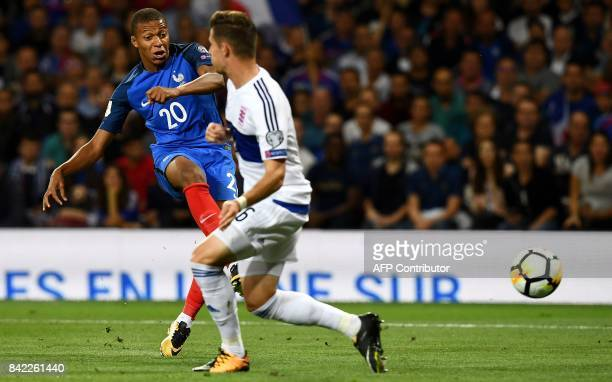 France's forward Kylian Mbappe shoots next to Luxembourg's midfielder Chris Philipps during the FIFA World Cup 2018 qualifying football match France...