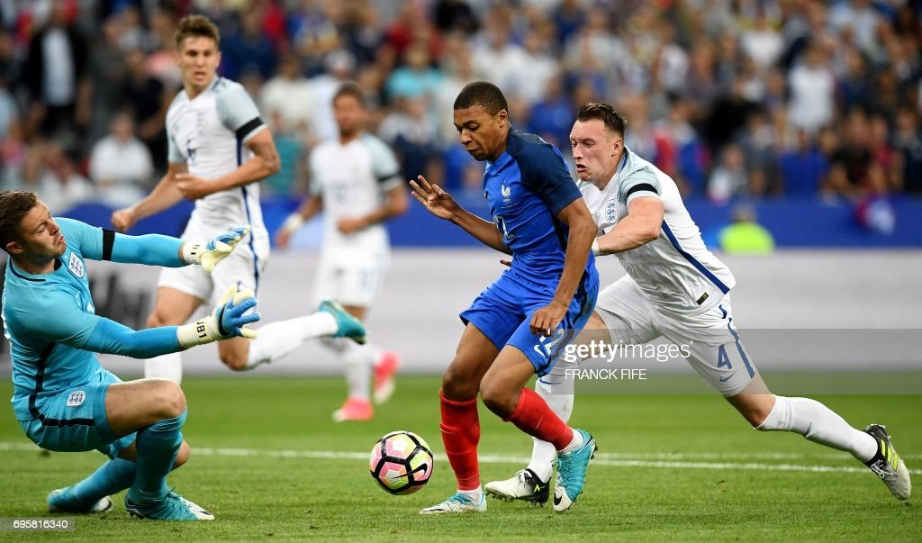 France's forward Kylian Mbappe (C) vies with England's goalkeaper Jack Butland (L) during the friendly football match France vs England on June 13, 2017 at the Stade de France stadium in Saint-Denis, north of Paris. /