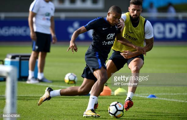 France's forward Kylian Mbappe vies with forward Olivier Giroud during a training session in Clairefontaine en Yvelines on August 28 as part of the...