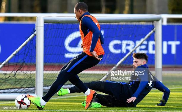 France's forward Kylian Mbappe vies with goalkeaper Benoit Costil during a training session in Clairefontaine near Paris on March 21 as part of the...