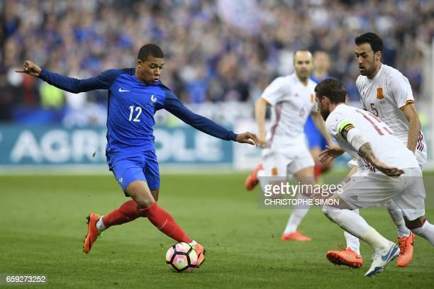 TOPSHOT France's forward Kylian Mbappe vies with Spain's midfielder Sergio Busquets and captain Sergio Ramos during their friendly football match...