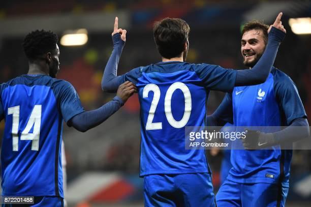 France's forward Martin Terrier is congratulated by France's forward Jonathan Bamba and France's midfielder Lucas Tousart after scoring a goal during...