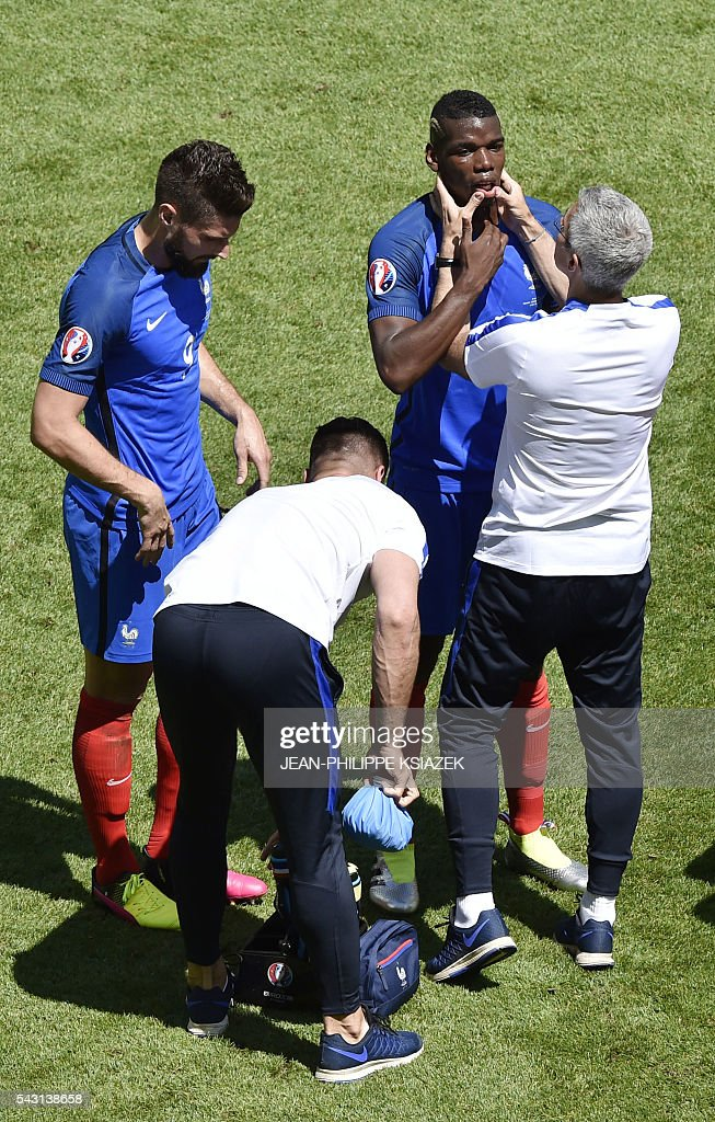 France's forward Olivier Giroud (L) and France's midfielder Paul Pogba (2R) get medical treatment during the Euro 2016 round of 16 football match between France and Republic of Ireland at the Parc Olympique Lyonnais stadium in Décines-Charpieu, near Lyon, on June 26, 2016. / AFP / JEAN
