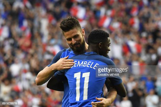 France's forward Olivier Giroud celebrates with France's forward Ousmane Dembele after scoring during the friendly football match between France and...