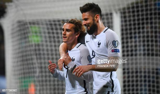 France's forward Olivier Giroud congratulates France's forward Antoine Griezmann after he scored a goal during the FIFA World Cup 2018 qualifying...