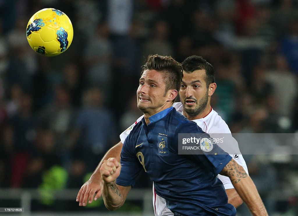 France's forward Olivier Giroud (L) eyes the ball in front Georgia's midfielder Akaki Khubutia during the FIFA World Cup 2014 qualifying football match Georgia vs France on September 6 2013 at the Boris Paichadze stadium in Tbilisi.