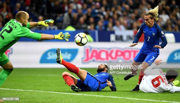 France's forward Olivier Giroud kicks the ball next t France's forward Antoine Griezmann and Belarus' goalkeeper Syarhey Chernik during the FIFA...
