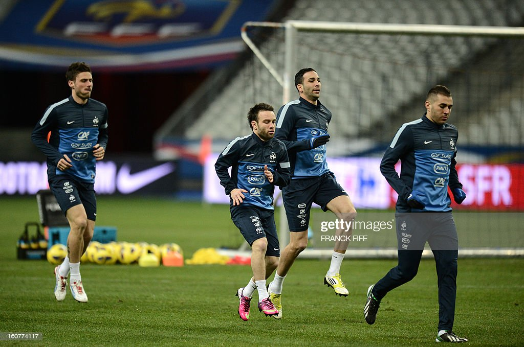 France's forward Olivier Giroud, midfielder Mathieu Valbuena, defender Adil Rami and forward Karim Benzema warm up a training session on February 5, 2013 at the Stade de France in Saint-Denis, near Paris, on the eve of a friendly international football match between France and Germany.