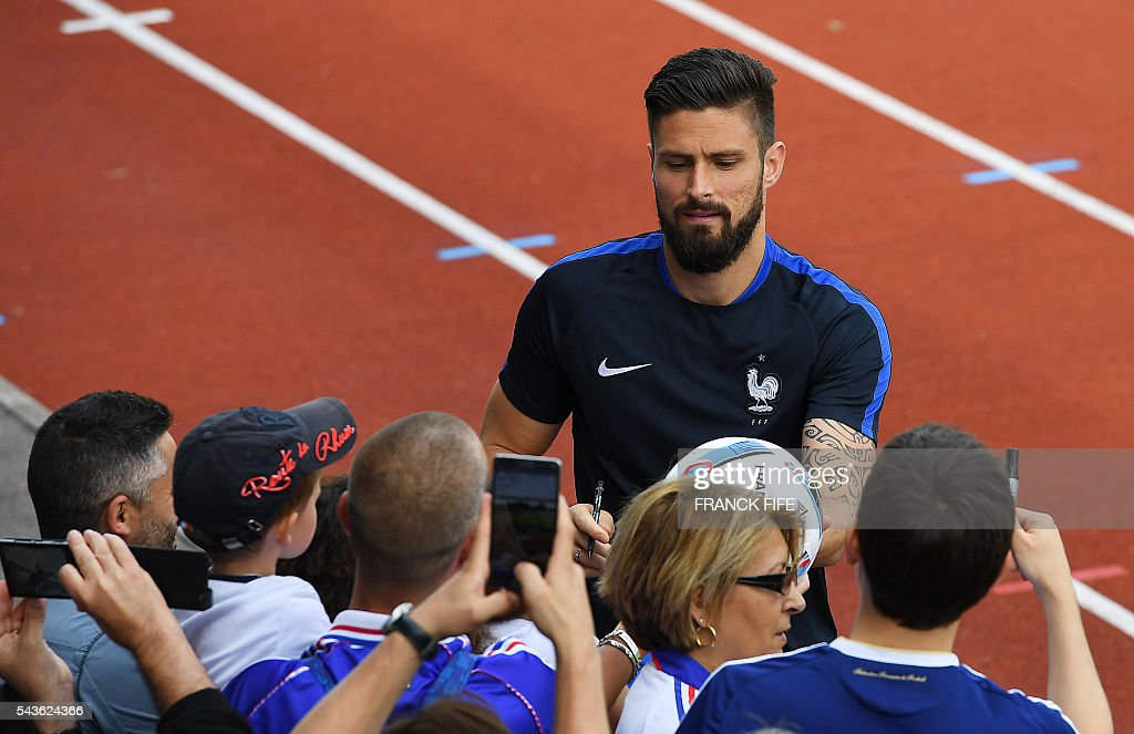 France's forward Olivier Giroud (C) signs autographs before a training session in Clairefontaine-en-Yvelines, southwest of Paris, on June 29, 2016, during the Euro 2016 football tournament. / AFP / FRANCK