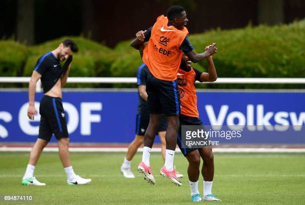 France's forward Ousmane Dembele and France's forward Alexandre Lacazette react at the end of a training session in ClairefontaineenYvelines near...